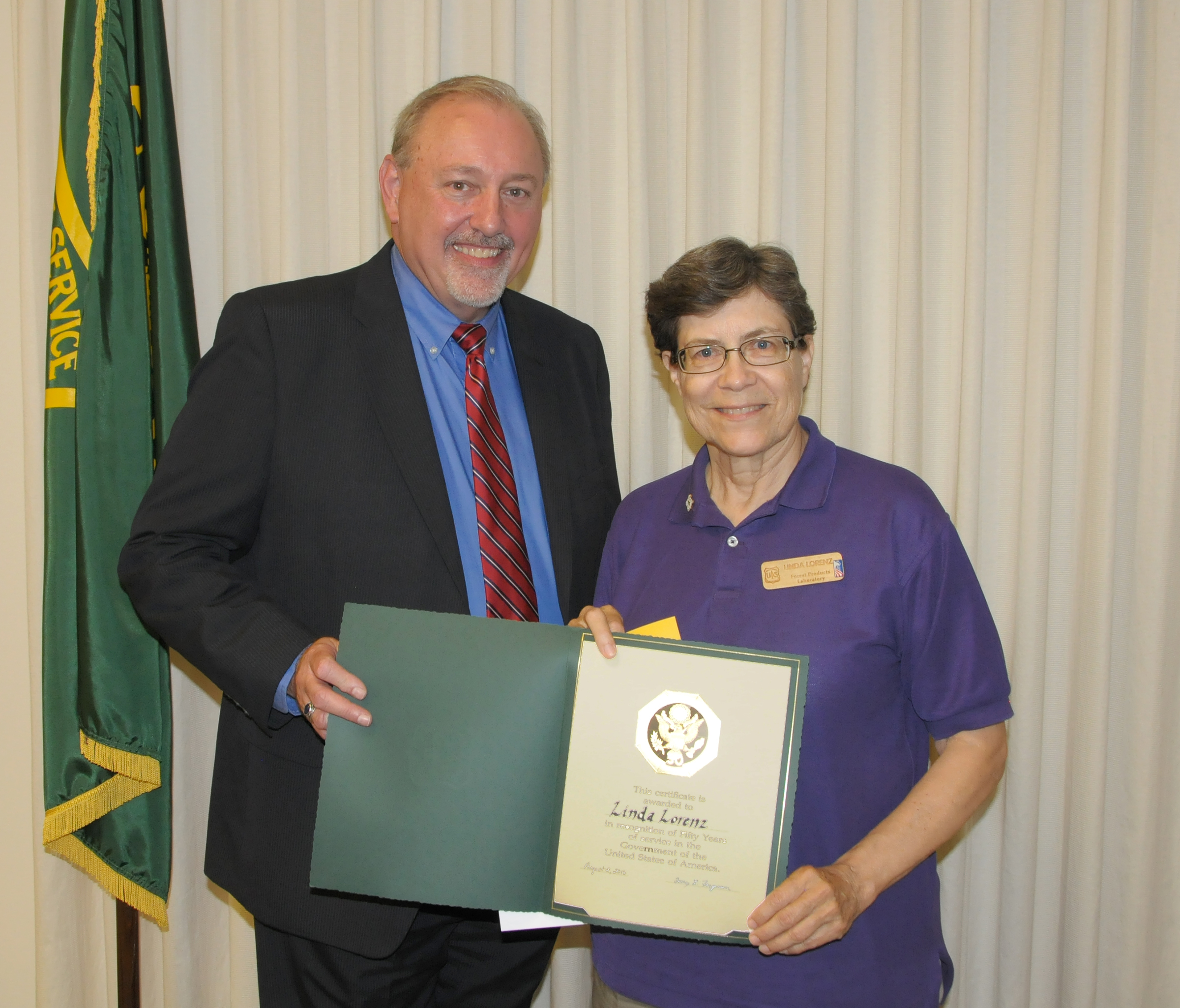 Linda Lorenz (right) accepts her 50 years of service certificate from Acting Director Tony Ferguson.